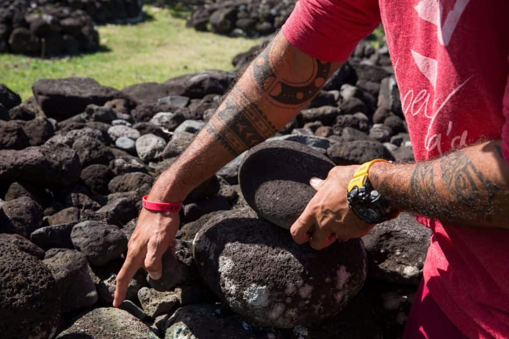 A man points at some volcanic rock