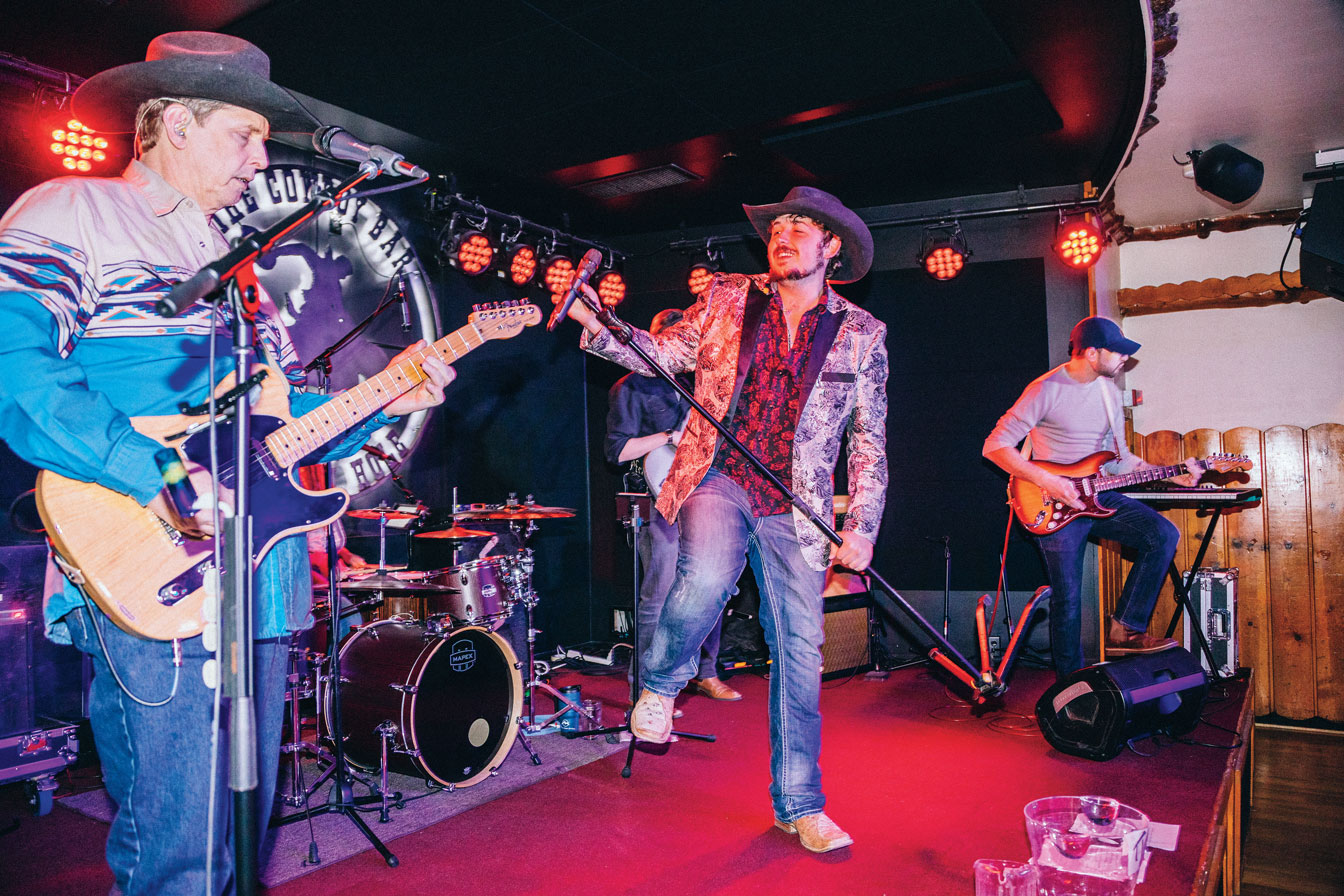 A band in cowboy hats performing on a stage.