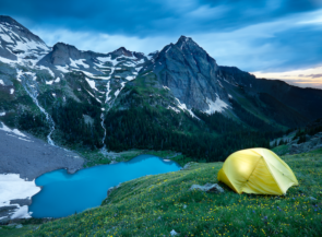 A yellow tent on a hill next to a mountain lake.