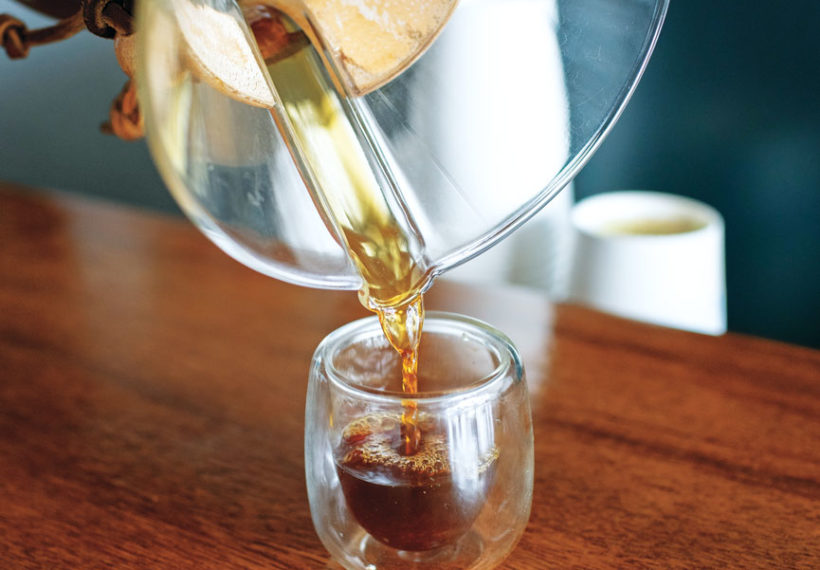 A coffee being poured in a small cup.
