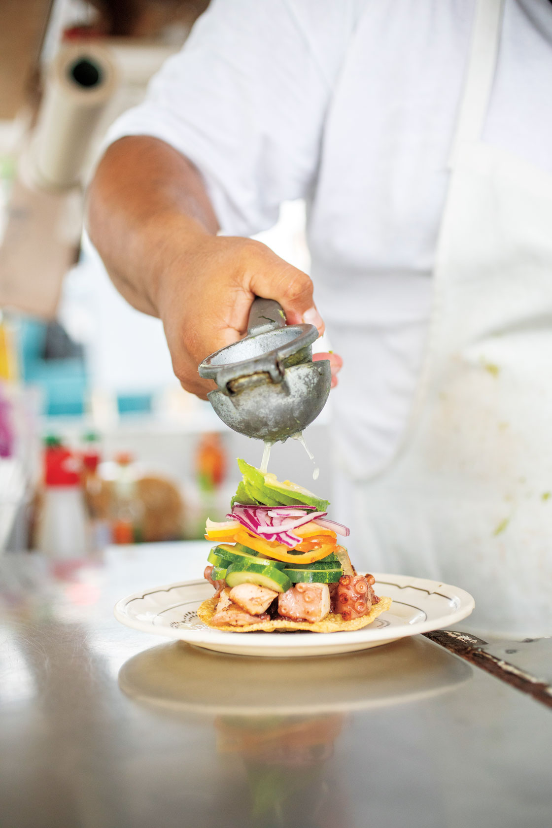 A chef squeezing fruit on a colorful dish.