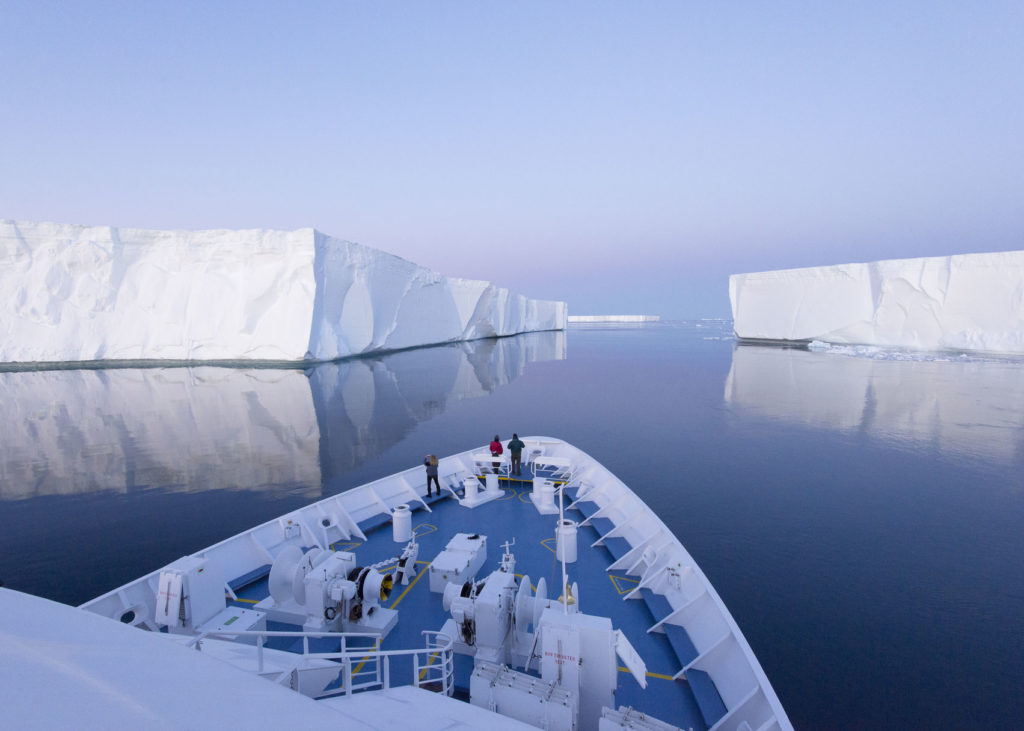 A ship floating next to two big icebergs