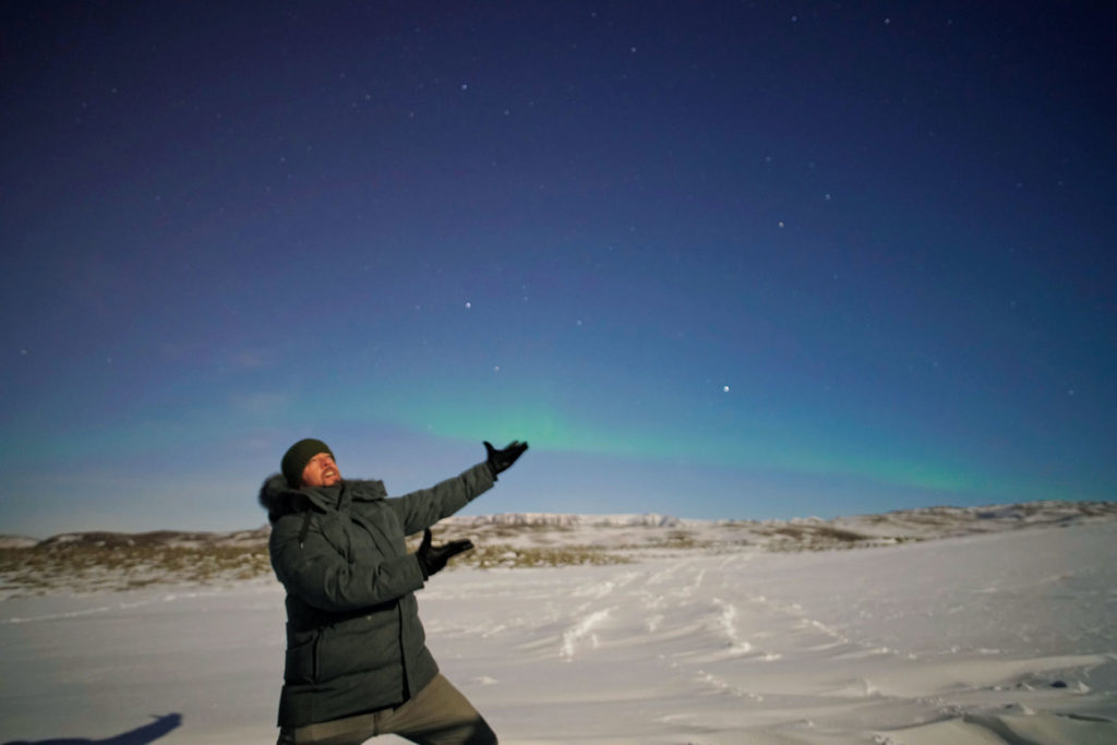 A man standing on snow next to the Northern Lights