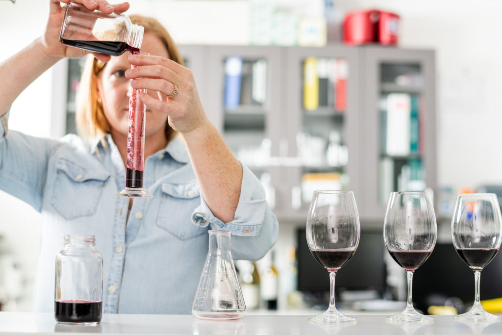 A woman pouring wine in glasses