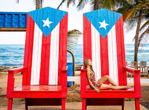 Woman lounges on two chairs painted with the Puerto Rican flag