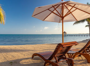 A pair of reclining beach chairs face the sunny horizon on the Sirenian Bay in Belize