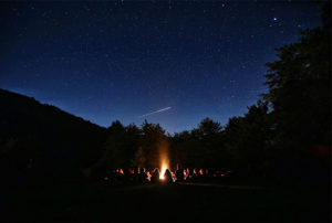A family sits around a cozy campfire while stargazing