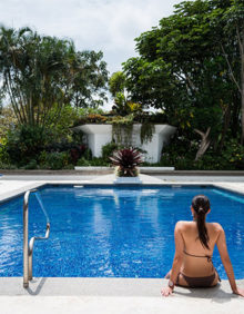Woman sits at the foot of a pool at the Hotel Bougainvillea in Costa Rica