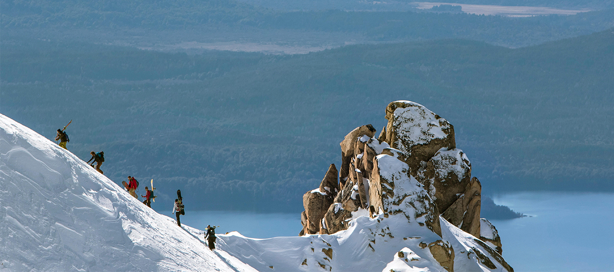 Six snowboarders scale a snowy slope in Argentina's Cerro catedral