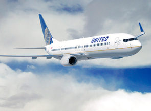 United 737-900ER plane in air amidst clouds